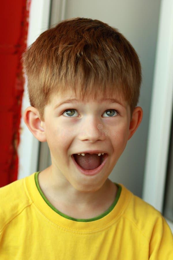 Portrait d'un garçon dans un T-shirt jaune dont les dents de lait supérieures avant ont tombé photo stock