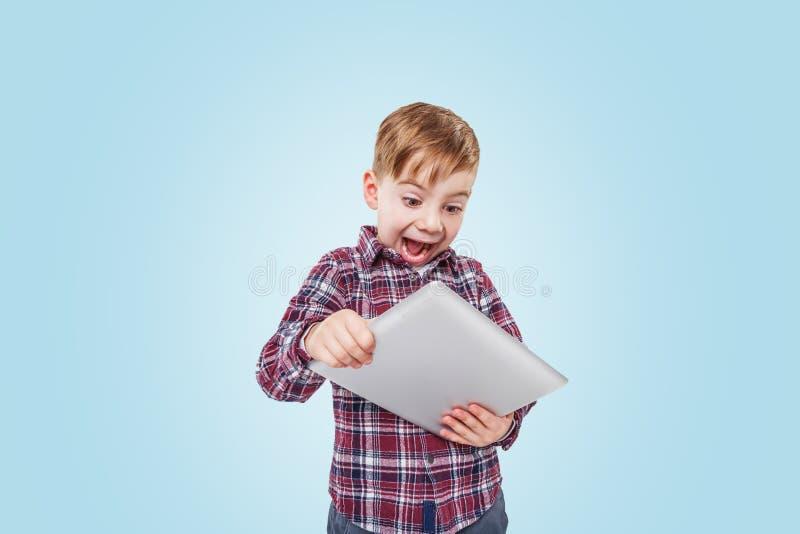 Portrait d'un garçon de sourire enthousiaste jouant la tablette APP photos libres de droits