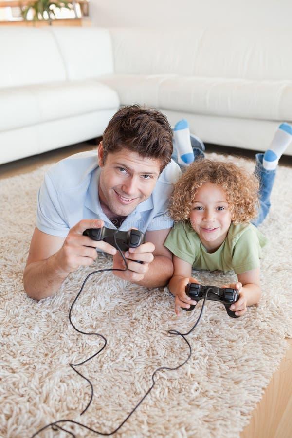 Portrait d'un garçon et de son père jouant des jeux vidéo photo stock