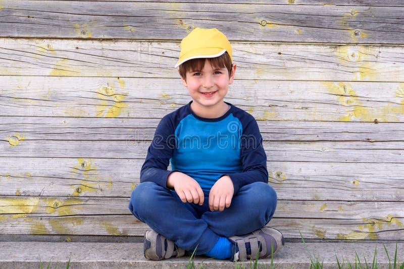 Portrait d'un garçon gai mignon avec le chapeau jaune se reposant dehors photos libres de droits