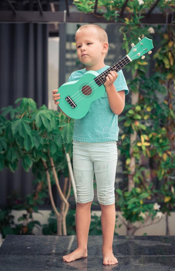 Portrait d'un garçon mignon avec l'ukulélé image stock