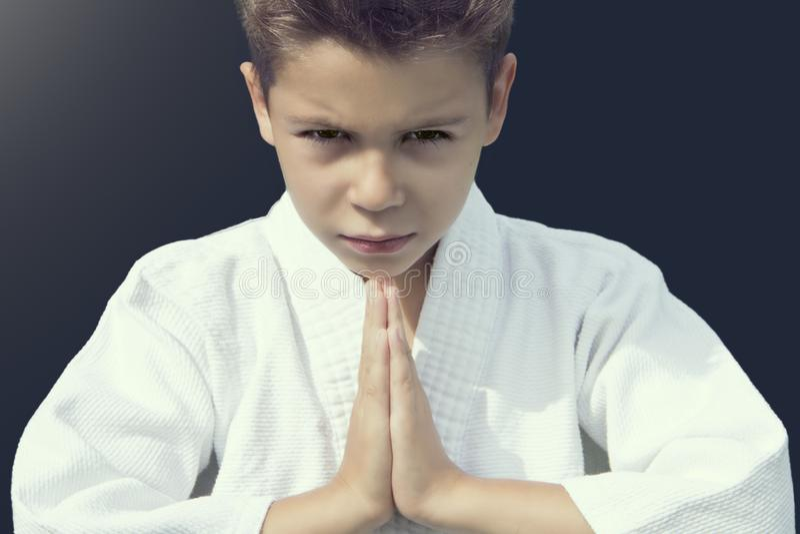 Portrait d'un garçon sérieux dans un kimono saluant son adversaire photos stock