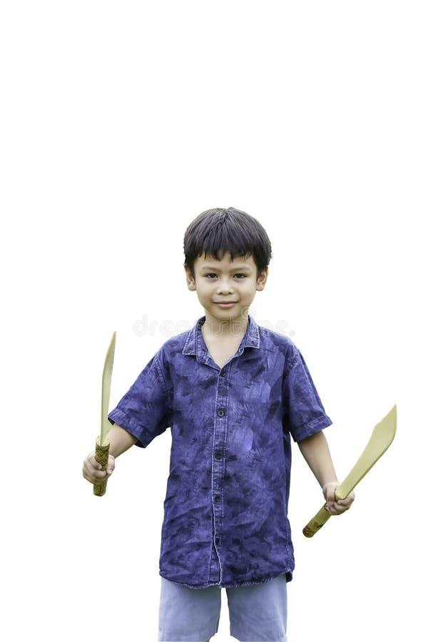 Portrait d'un garçon tenant un jeu en bois d'épée sur un fond blanc photo stock