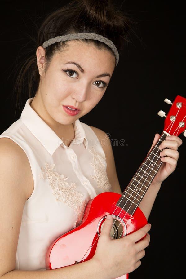 Portrait d'un gilr de l'adolescence jouant une ukulélé sans le sourire photos libres de droits