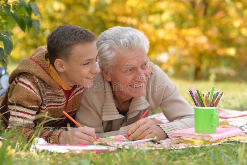 Portrait d'un grand-père et de son petit-fils dessinant à l'extérieur images libres de droits
