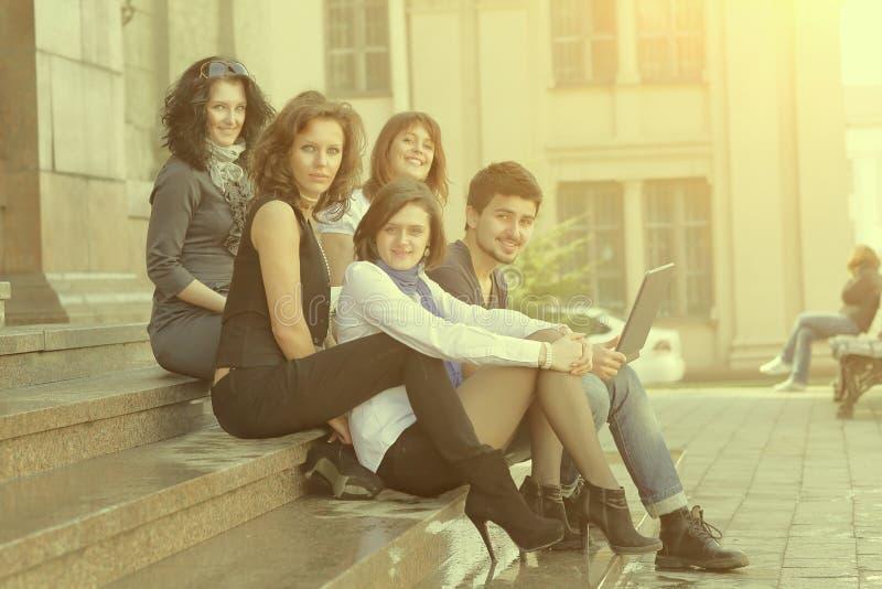 Portrait d'un groupe d'étudiants s'asseyant devant l'université photographie stock libre de droits
