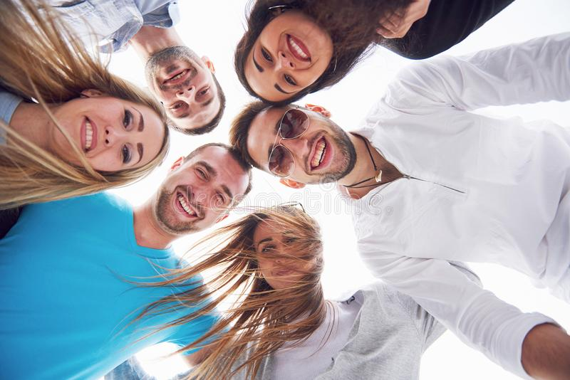 Portrait d'un groupe des jeunes s'asseyant au bord du pilier, dehors en nature Amis appréciant un jeu sur photographie stock