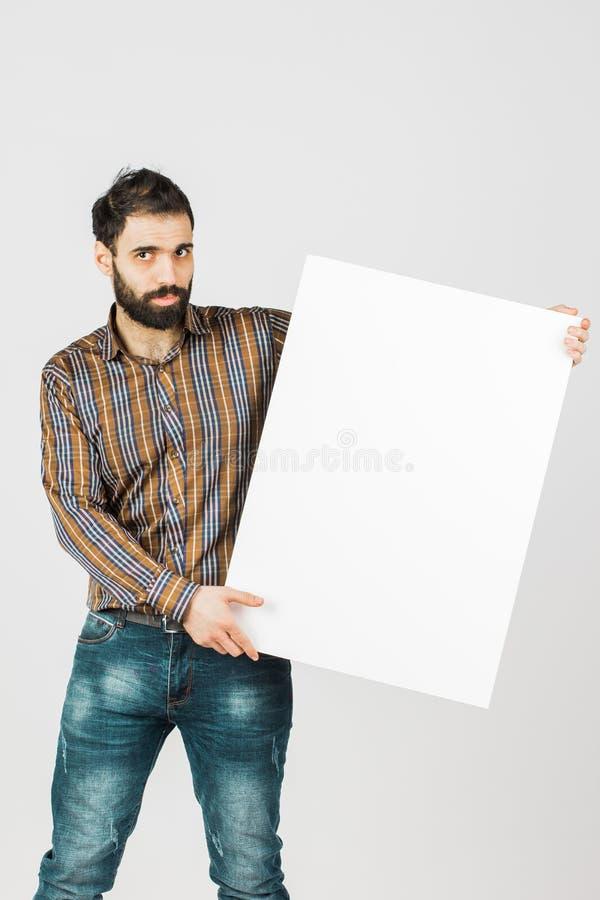 Portrait d'un homme d'affaires barbu tenant un panneau vide blanc W images stock