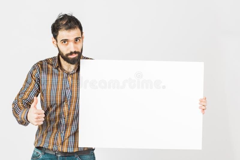 Portrait d'un homme d'affaires barbu tenant un panneau vide blanc W image libre de droits