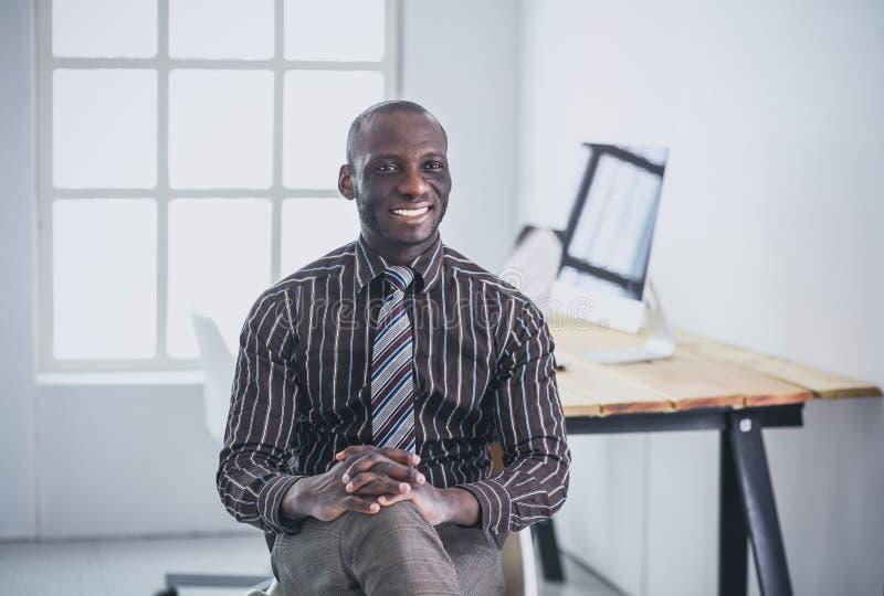 Portrait d'un homme d'affaires noir bel s'asseyant dans le bureau photos stock