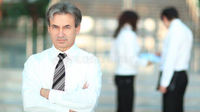 Portrait d'un homme d'affaires sup?rieur sur le bureau brouill? de fond photographie stock libre de droits