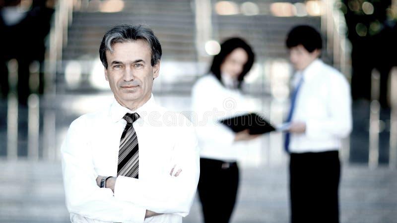 Portrait d'un homme d'affaires sup?rieur sur le bureau brouill? de fond photographie stock