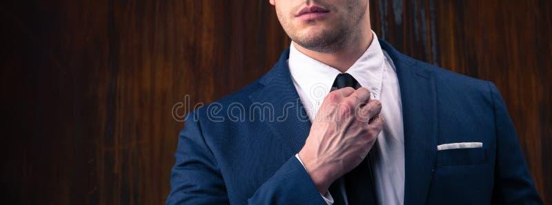 Portrait d'un homme d'affaires sur le fond en bois noir images stock