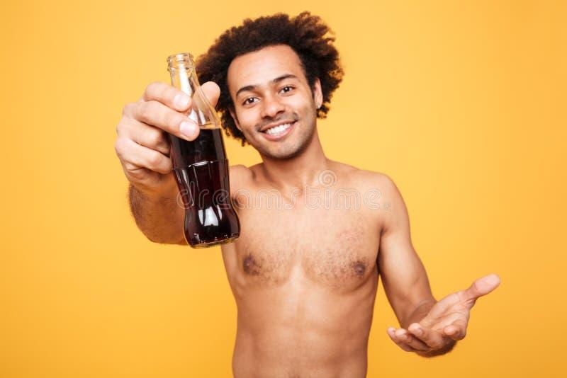 Portrait d'un homme africain happyahirtless montrant la bouteille avec le liquide photo stock