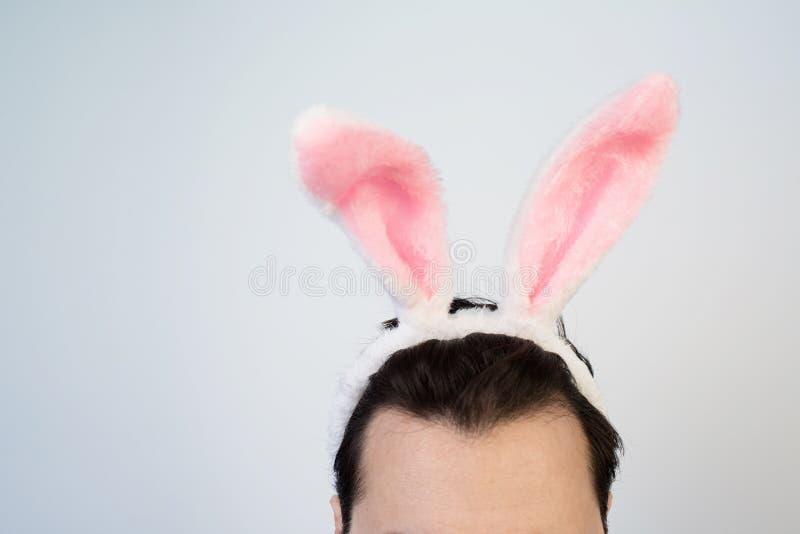 Portrait d'un homme avec cligner de l'oeil rose d'oreilles de lapin d'isolement sur un fond blanc photographie stock