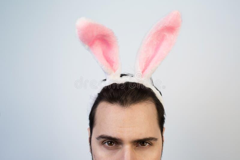 Portrait d'un homme avec cligner de l'oeil rose d'oreilles de lapin d'isolement sur un fond blanc photo stock