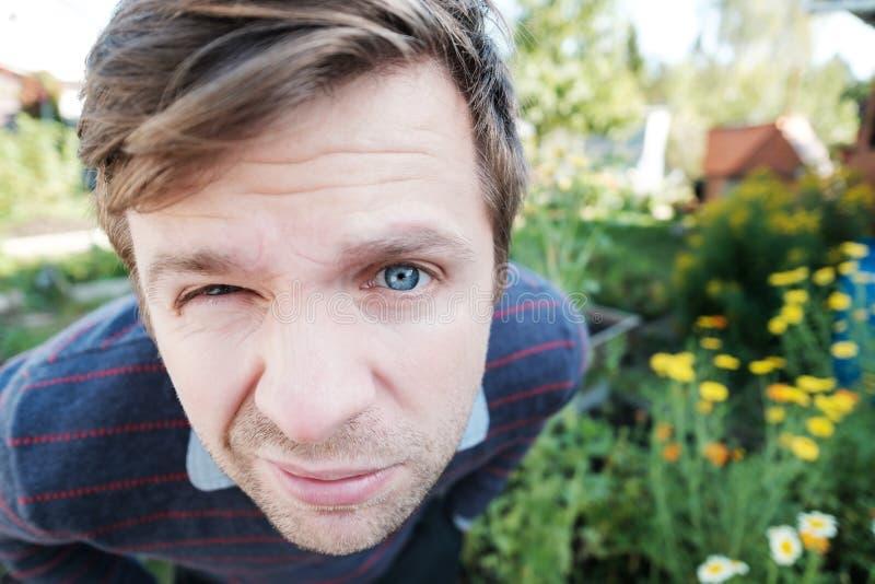 Portrait d'un homme avec des yeux bleus regardant l'appareil-photo avec l'interrogation et l'expression du visage méfiante photos stock
