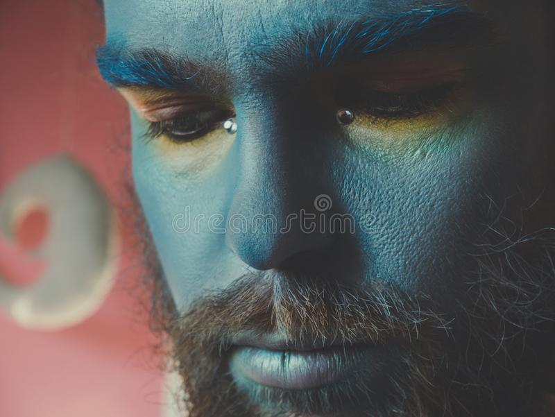 Portrait d'un homme avec un maquillage bleu sur son visage Présentez le maquillage, comme un étranger, imagination image stock
