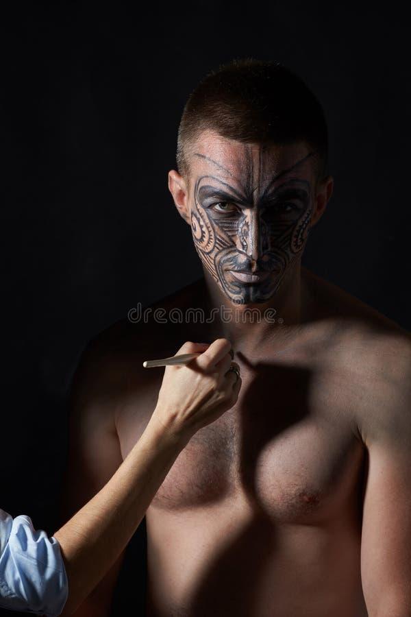Portrait d'un homme avec un tatouage sur son visage dans le style d'un mA images libres de droits