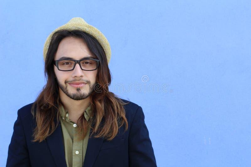 Portrait d'un homme barbu dans un costume et un chapeau qui pose au-dessus du fond bleu avec l'espace de copie photographie stock libre de droits