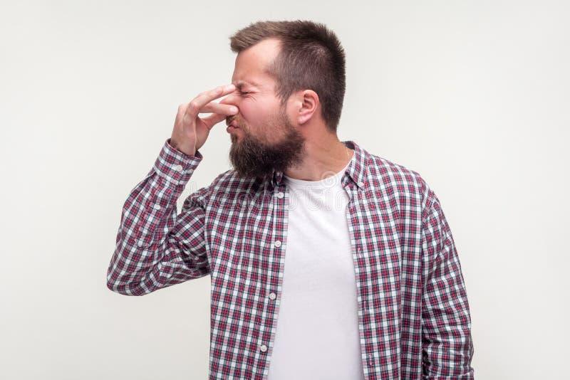 Portrait d'un homme barbu insatisfait qui pince le nez avec une grimace dégoûtante studio intérieur photographié isolé sur fond b image stock