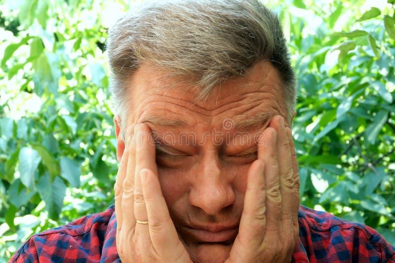 Portrait d'un homme beau, fatigué, surmené, supérieur, qui frotte ses yeux avec ses doigts Soumis à une contrainte, somnolent, ép photos libres de droits