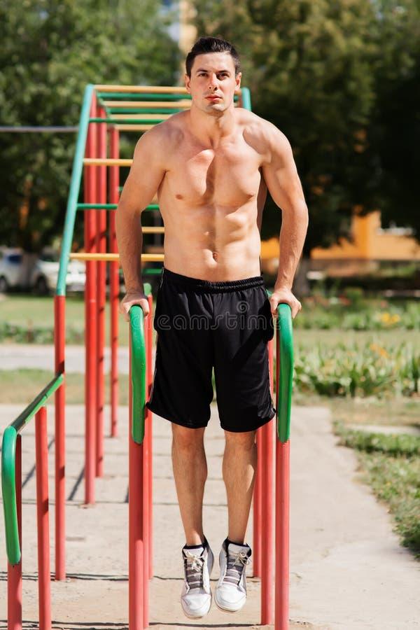 Portrait d'un homme bel faisant l'exercice sur des barres parallèles en parc image stock