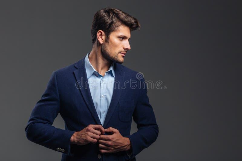 Portrait d'un homme boutonnant sa veste et regardant loin photos stock