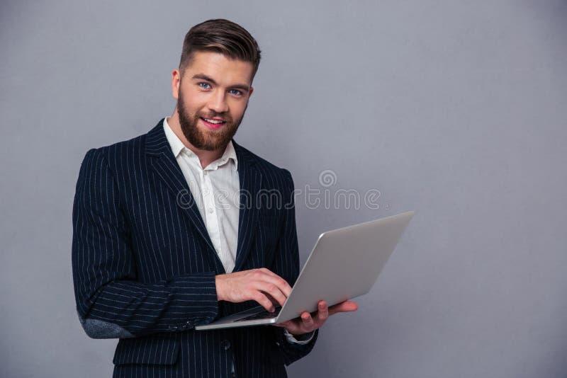Portrait d'un homme d'affaires de sourire utilisant le lapto photographie stock