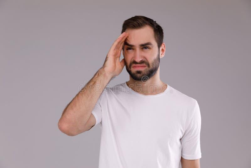 Portrait d'un homme dans un T-shirt blanc sur un fond gris Retenir sa tête photographie stock
