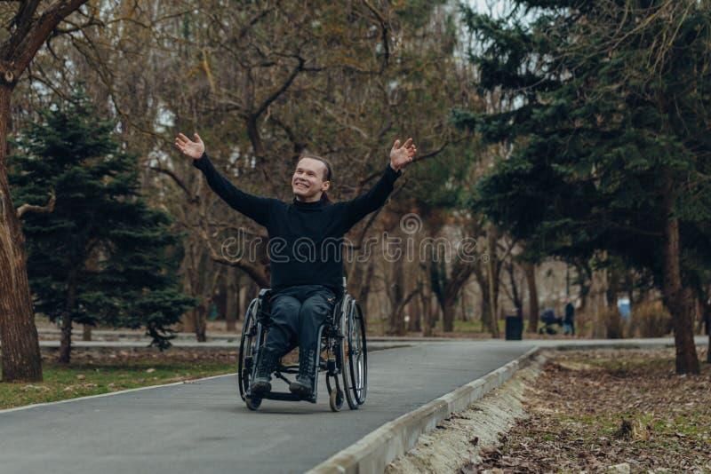 Portrait d'un homme heureux sur un fauteuil roulant en parc photos libres de droits