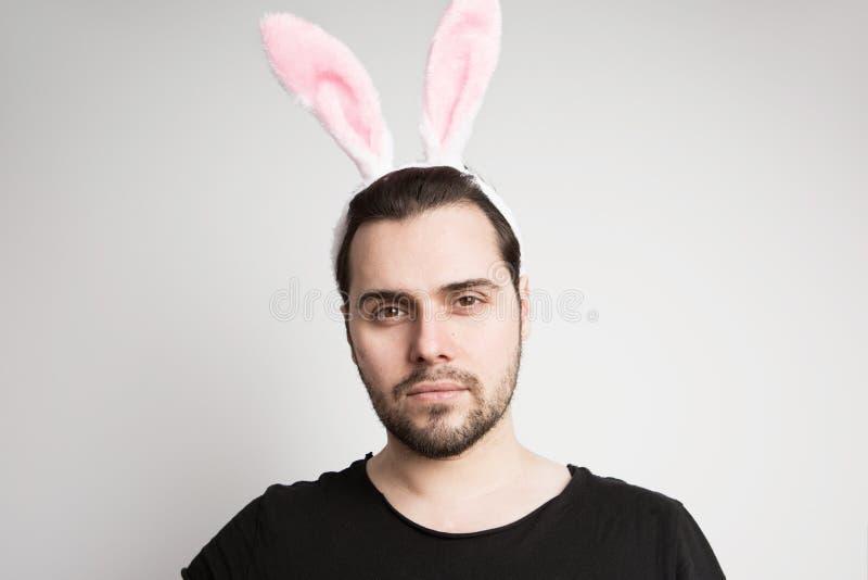 Portrait d'un homme hispanique avec cligner de l'oeil rose d'oreilles de lapin d'isolement sur un fond blanc photo libre de droits