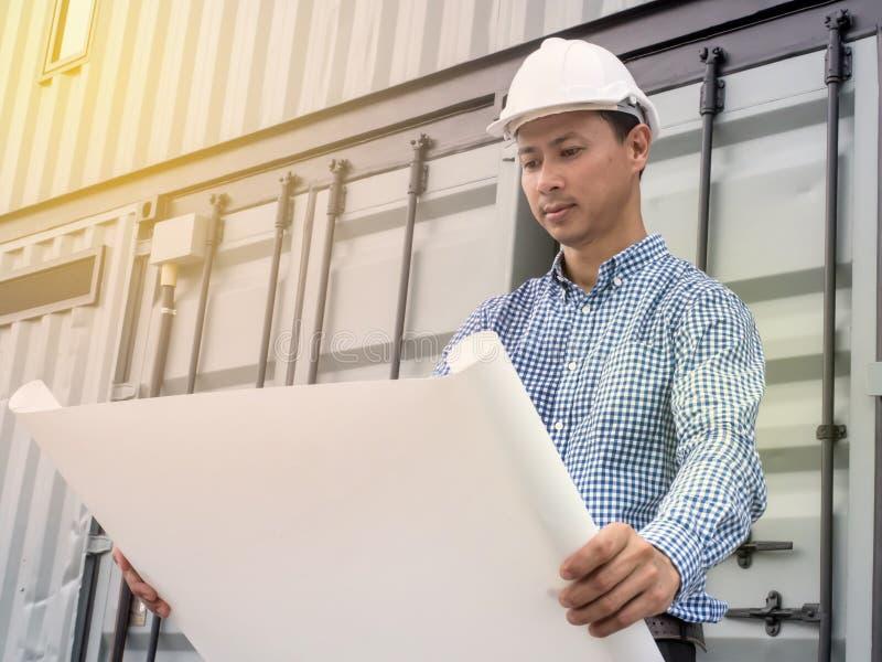 Portrait d'un homme d'ingénieur avec le casque regardant les plans de papier le chantier de construction, ingénieur de projet photographie stock libre de droits