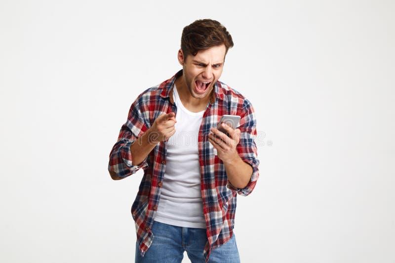 Portrait d'un homme mécontent fâché regardant le téléphone portable image libre de droits
