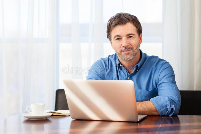 Portrait d'un homme mûr ayant un petit sourire, sur un fond de rideaux photos libres de droits