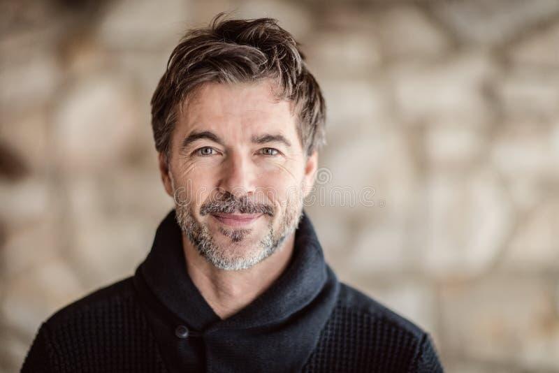 Portrait d'un homme mûr souriant à l'appareil-photo photo stock