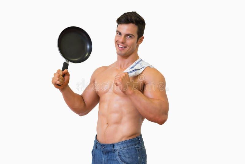 Portrait d'un homme musculaire sans chemise tenant la poêle photographie stock libre de droits