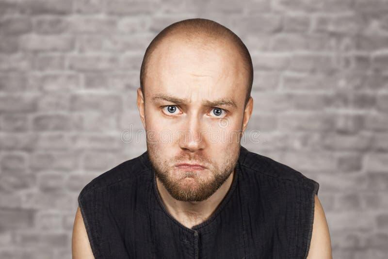Portrait d'un homme offensé bouleversé chauve éprouvant l'effort dû aux problèmes sur un fond de mur de briques images libres de droits
