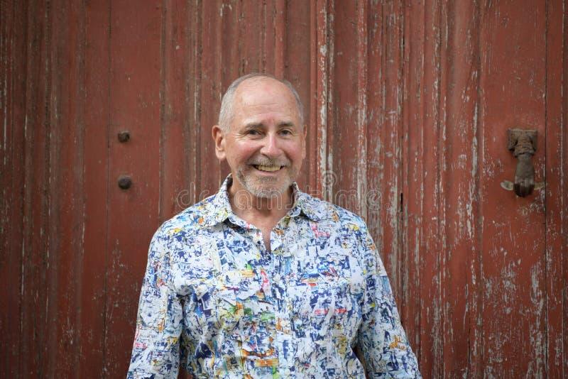 Portrait d'un homme plus âgé souriant sur le fond rouge photo stock