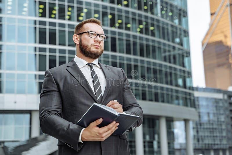 Portrait d'un homme réussi d'affaires avec un carnet dans des ses mains sur le fond du centre d'affaires image libre de droits