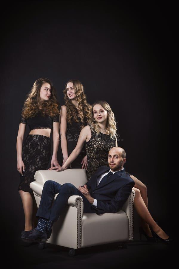 Portrait d'un homme s'asseyant dans une chaise et entouré par de belles filles dans des robes égalisantes noires images libres de droits