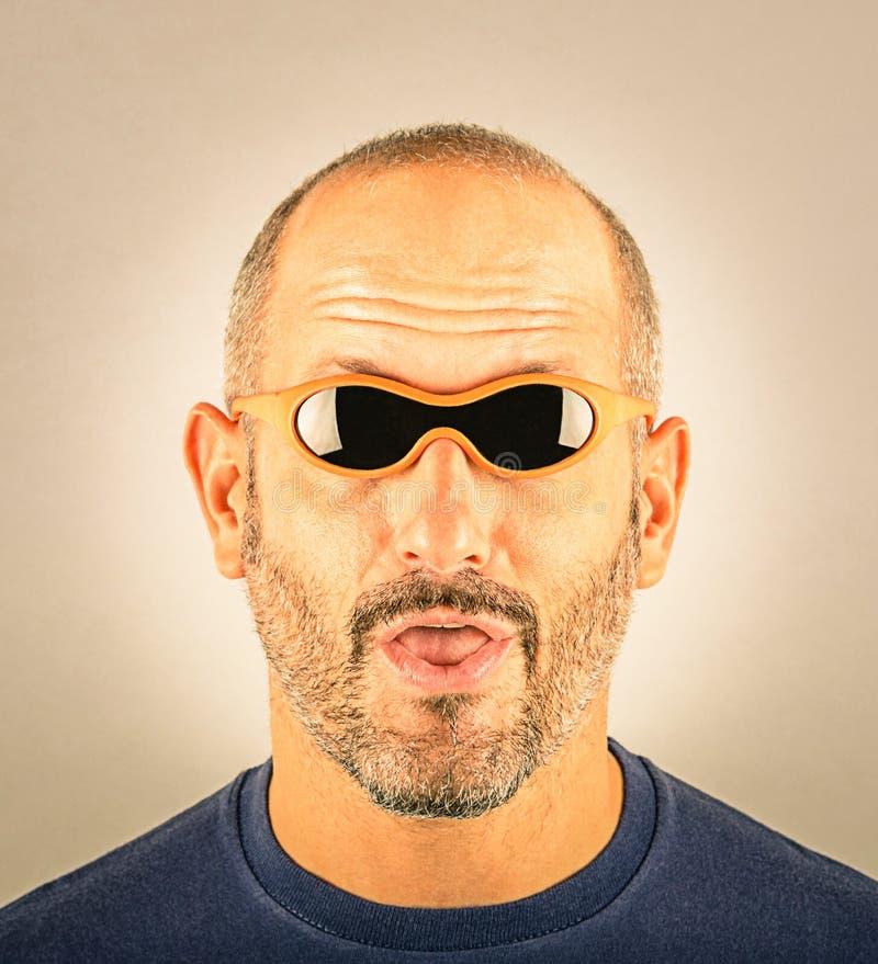 Portrait d'un homme stupide avec les lunettes de soleil trop petites photographie stock libre de droits
