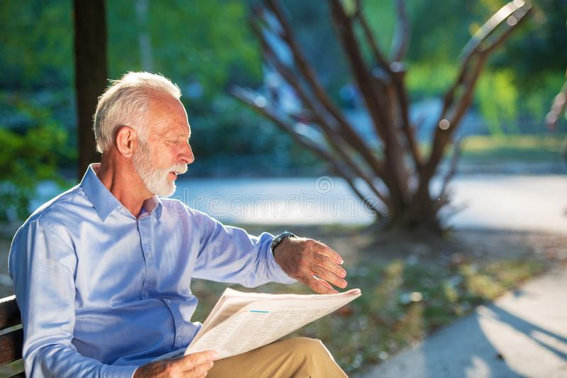 Portrait d'un homme supérieur lisant des journaux en parc photos stock