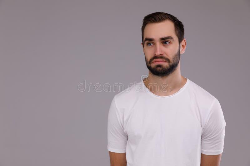 Portrait d'un homme triste dans un T-shirt blanc sur un fond gris photo stock
