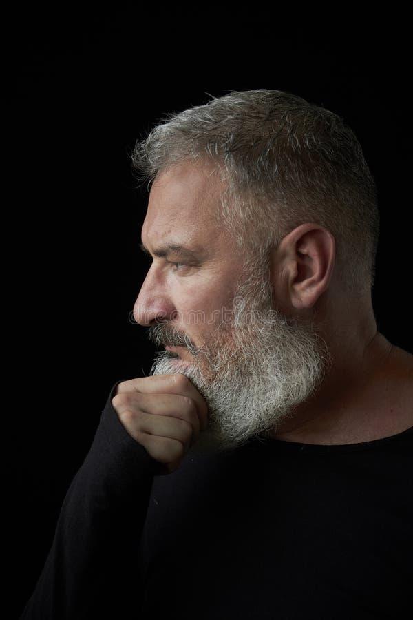 Portrait d'un homme d'une chevelure gris brutal avec une barbe luxuriante grise et un visage strict sur un fond noir, foyer sélec image libre de droits