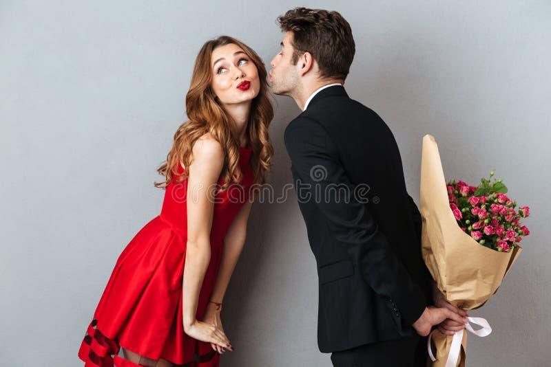 Portrait d'un jeune beau couple embrassant tout en se tenant photos stock