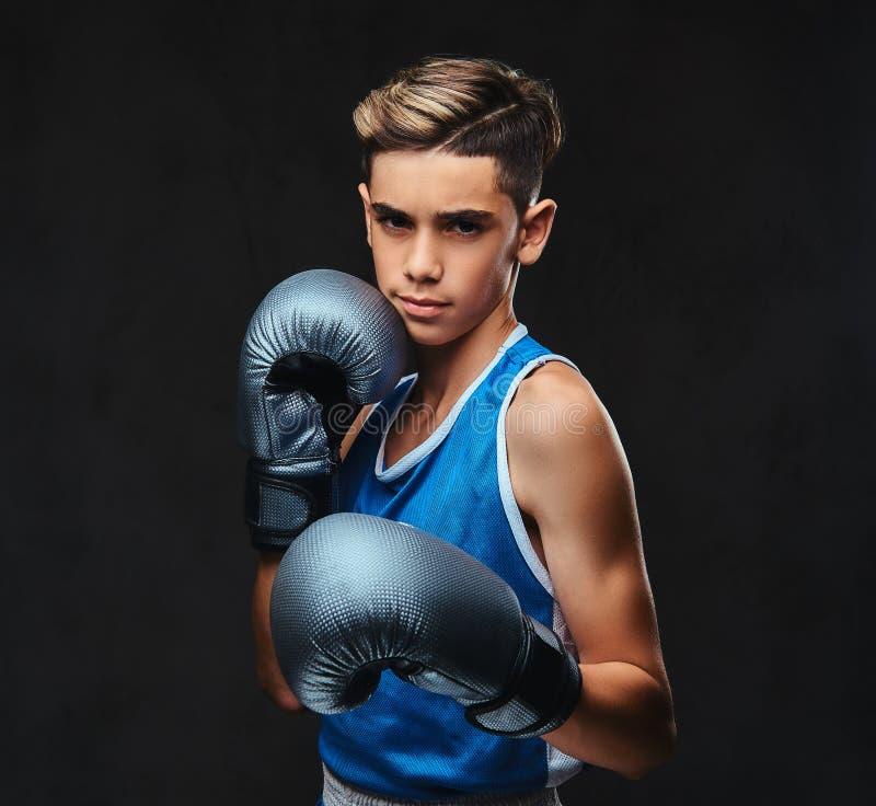 Portrait d'un jeune boxeur beau dans les gants de port de vêtements de sport D'isolement sur le fond foncé images stock