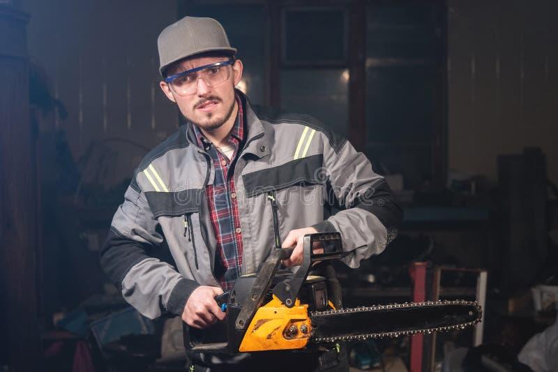 Portrait d'un jeune charpentier tenant dans des ses mains une tronçonneuse menaçant la visionneuse par des menaces Violation de l photos stock