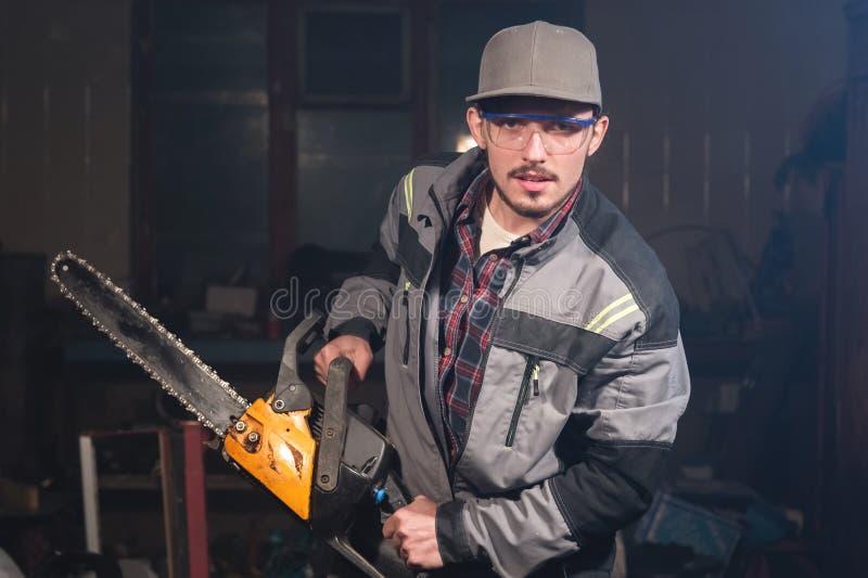 Portrait d'un jeune charpentier tenant dans des ses mains une tronçonneuse menaçant la visionneuse par des menaces Violation de l photos libres de droits