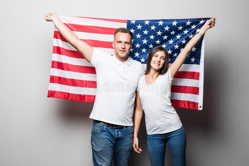 Portrait d'un jeune couple heureux sur le fond du drapeau des USA 4 juillet photo stock